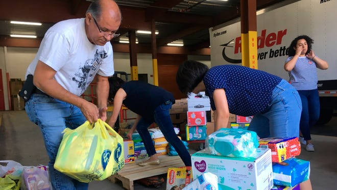 A Catholic Charities of Rio Grande Valley staffer and volunteers unload boxes of donations on to a cart at a storage facility in McAllen, Texas, on June 24, 2018.