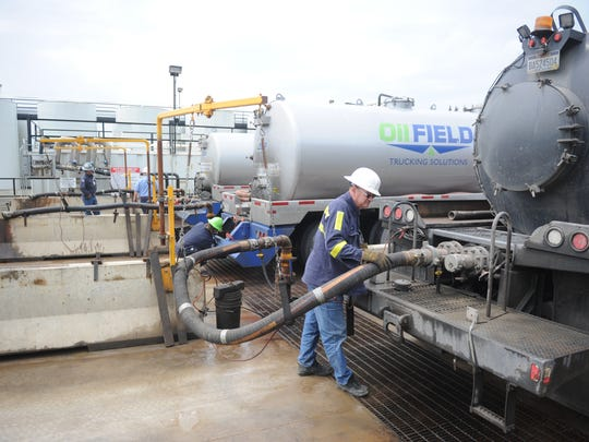 An employee of Central Environmental Services, right, unloads flowback water at Buckeye Brine in this file photo. Buckeye President Steve Mobley said the oil and gas industry can have its ups and downs and taking other forms of liquid waste that can be safely injected into the ground is a move that positions the company for the future.