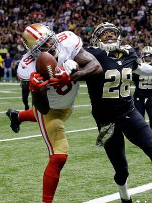 San Francisco 49ers' wide receiver Anquan Boldin (left) pulls in a touchdown reception in front of New Orleans Saints' cornerback Keenan Lewis in the 49ers' 27-24 win in overtime Sunday. Lewis injured his left knee trying to break up a pass to Boldin.