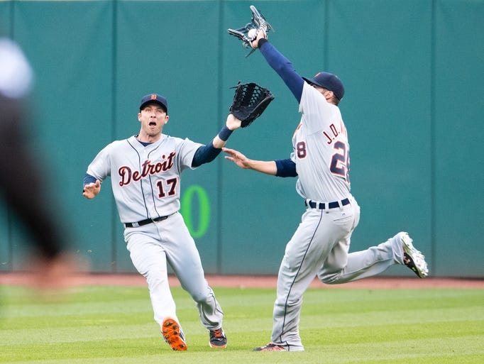 Tigers' outfielders Andrew Romine, left, and J.D. Martinez