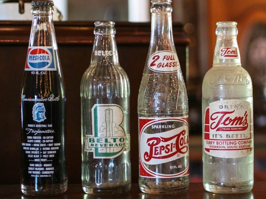 From left, a commemorative Anderson College Pepsi bottle (1974),  Belton Beverage, Pepsi (1945), and Tom's from Terry Bottling Company in Anderson were bottled in Anderson County.
