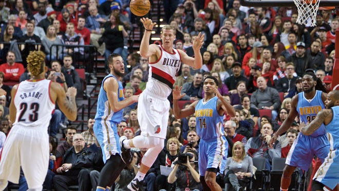 Portland Trail Blazers center Mason Plumlee, center, passes the ball during the first half of an NBA basketball game in Portland, Ore., Wednesday, Dec. 30, 2015.