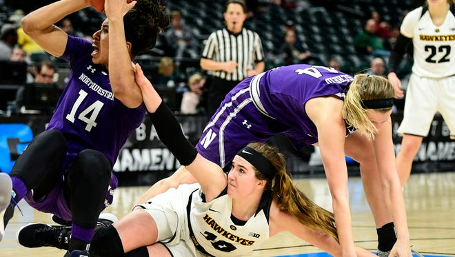 Northwestern forward Pallas Kunaiyi-Akpanah (14) tries to pass the ball against Iowa forward Megan Gustafson.