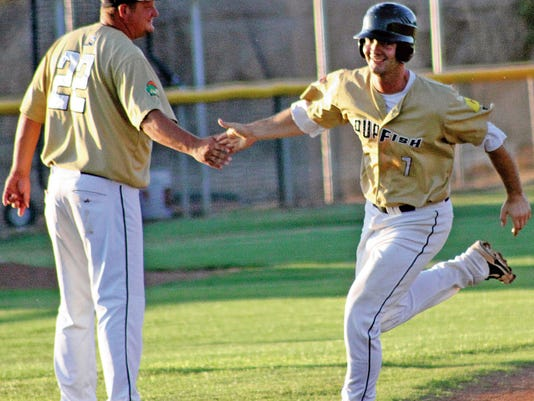 Michael Brandi, a former White Sands Pupfish, is congratulated by field manager Mickey Speaks on July 1, 2015.