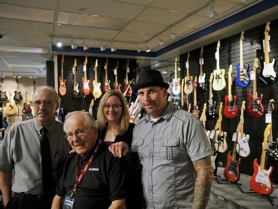 Larry Miller, front, owner of Metronome Music, is surrounded