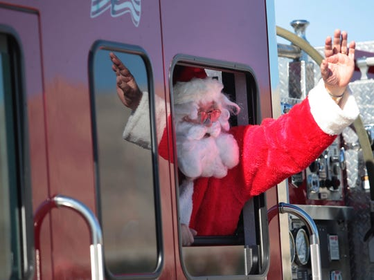Santa waves to the crowd from a fire truck during Saturday's Desert Hot Springs Holiday Parade.