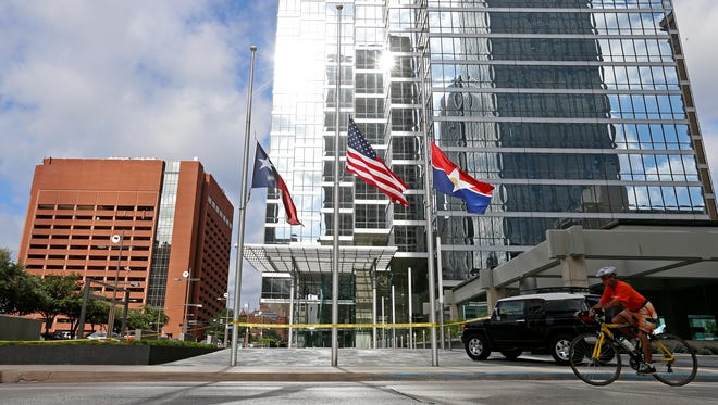 A person rides a bike under the Texas State, U.S. and City of Dallas flags flown at half-staff at Bank of America Plaza in honor of the police officers killed by snipers in Dallas, Friday.