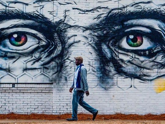 A pedestrian walks past a mural in Birmingham, Ala.