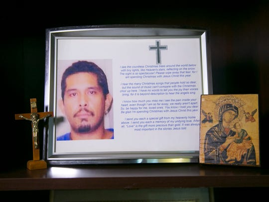 A crucifix and image of the Virgin Mary flank a photo