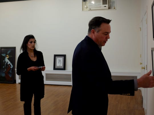 Al and Tina Magonagle hang paintings by Robert Hochgertel in the new Pitman Gallery and Art Center.