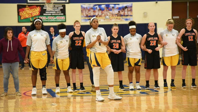 The Loveland and Walnut Hills girls basketball teams locked arms in unity during the National Anthem Feb. 7 at Walnut Hills.