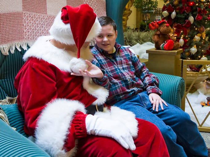 Hudson Robbins, 11, Indianapolis, checks out part of Santa's hat during his visit. Children with special needs had an opportunity to visit with Santa Claus Sunday, December 8, 2013, at Washington Square mall, where precautions were taken to make the setting a calming experience.