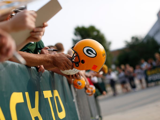 Fans hold out items to be autographed by Green Bay Packers players during training camp practice at Ray Nitschke Field on Friday, Aug. 1, 2014. Evan Siegle/Press-Gazette Media