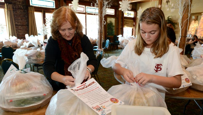 Weezie Carlson and Callie Mitchell wrap up Thanksgiving dinners with fried turkeys in 2013 for around 130 families in need.