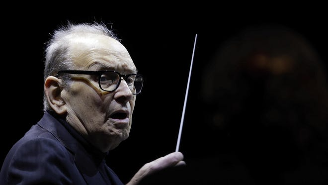 """Italian composer Ennio Morricone directs an ensemble during a concert of his """"60 Year Of Music World Tour"""" in Milan, Italy, Tuesday, March 6, 2018."""