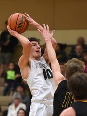 Manogue's Kolton Frugoli goes up to shoot with Galena's Moses Wood attempting to block the shot during Tuesday's game at Bishop Manogue.