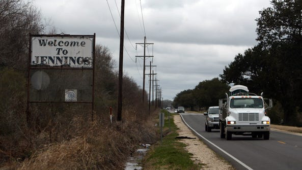 A rusted, chipped sign welcoming motorists to Jennings