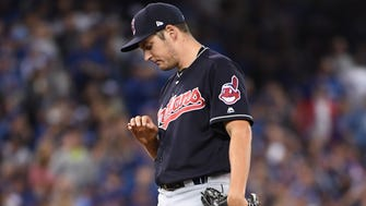 Cleveland Indians starting pitcher Trevor Bauer looks at his bleeding finger during the first inning in Game 3 of the 2016 ALCS.