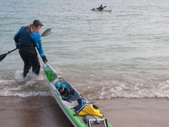 Traci Lynn Martin pulls her kayak into Lake Huron as she launches at Lighthouse Beach in Port Huron