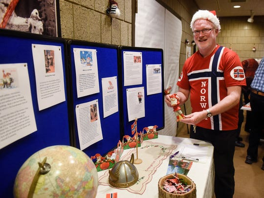 Frank Haynes holds a statue of Jule Nisse during KringleFest Saturday, Dec. 2, at the Stearns History Museum in St. Cloud.