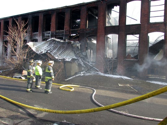 Firefighters stand in front of the charred shell of a warehouse that burned Sunday night in Elmira Heights.