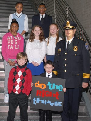 Bottom row, from left: Colin J. Kosmicki Zappolo, Nickolas Trouskie-St. Louis (with sign), Police Chief Michael L. Ciminelli. Middle row, from left: Jacqueline Lynn, Ryan Springer, Shaughnessy Flaherty. Top row, from left, Javine Overton-Balkam, Kashawn Porter.