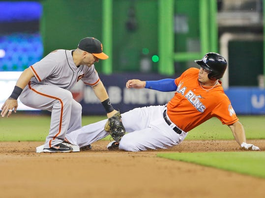 Miami Marlins' Giancarlo Stanton steals second base as San Francisco Giants second baseman Marco Scutaro is unable to make the tag during the first inning of a baseball game, Sunday, July 20, 2014 in Miami. (AP Photo/Wilfredo Lee)