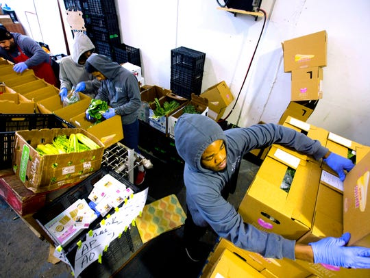 "Imperfect Produce operation associates, Larry Mitchell, right, stacks assembled boxes of ""ugly"" fruits and vegetables. The San Francisco company then delivers the produce to your home. The saving of purchasing these imperfect produce can be 25-50 percent off prices at the grocery store."