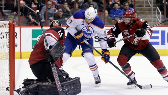 Edmonton Oilers left wing Milan Lucic (27) scores on Arizona Coyotes goalie Mike Smith (41) while getting pressured by defenseman Alex Goligoski (33) in the first period during an NHL hockey game, Wednesday, Dec. 21, 2016, in Glendale, Ariz.
