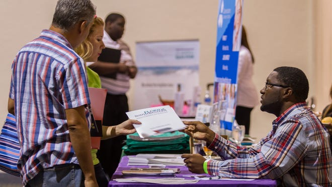 From right, Jackie Beard, an enrollment specialist at Florida SouthWestern State College, speaks with Joan Garcia and David Guatarasma during a job fair at Harborside Event Center in Fort Myers.