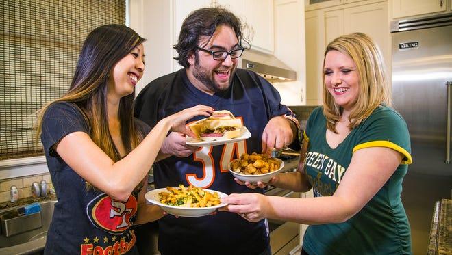 Kellie Hwang, Dominic Armato and Jennifer McClellan dish over Super bowl food.