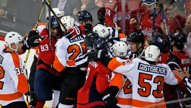 The Washington Capitals and Philadelphia Flyers are separated by officials as time expired in Game 1 of a first-round NHL hockey Stanley Cup playoffs series, Thursday,  in Washington.