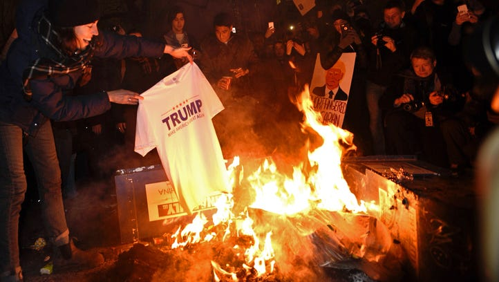 Demonstrators burned a Trump T-shirt as they gathered around a fire on K St. NW in Washington.