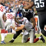 Giants quarterback Eli Manning is sacked by Eagles nose tackle Bennie Logan during New York's 27-0 loss Sunday.