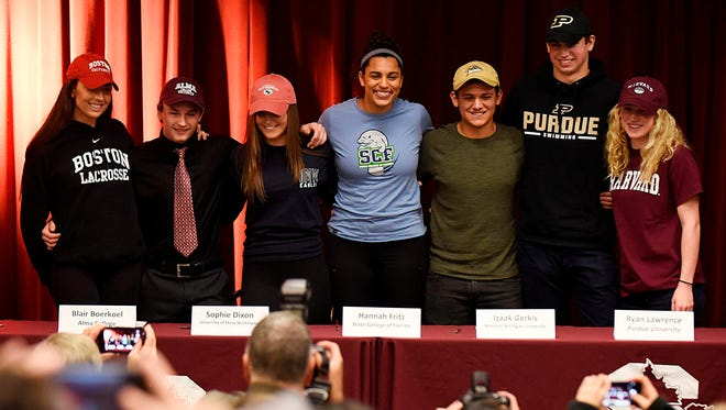 Seven Seaholm student athletes pose for photos in the Little Theater after announcing their college intentions Tuesday afternoon.