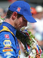 IndyCar driver Alexander Rossi pauses with the wreath around his neck after winning the 100th running of the Indianapolis 500, Indianapolis Motor Speedway, Sunday, May 29, 2016.