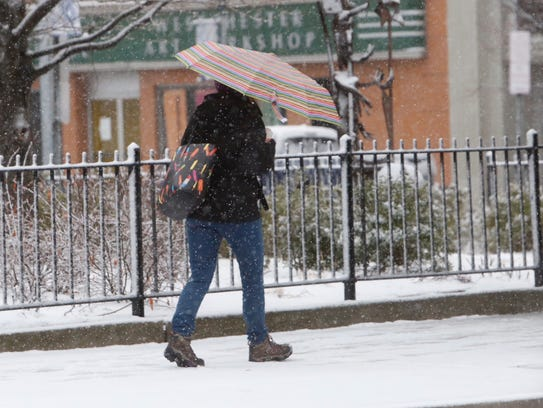 A pedestrian makes her way along the street in Peekskill