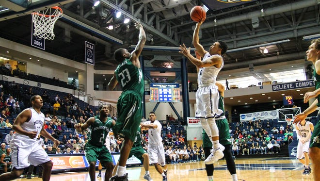 Monmouth's Justin Robinson shoots over a Manhattan defender during a game last year in West Long Branch. The Hawks lost an emotional game at Manhattan Thursday night.