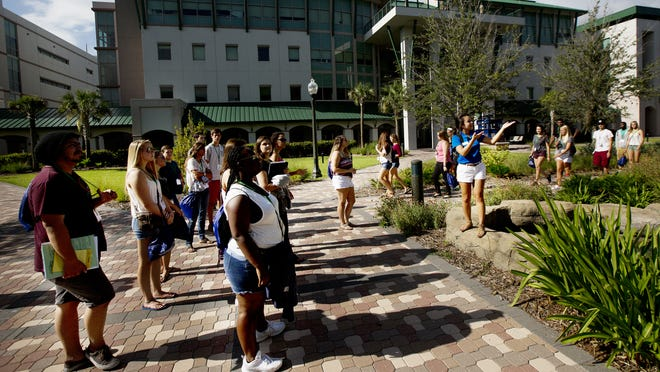 Incoming FGCU  freshman get a tour of the campus during their orientation. Giving them information about the campus is  student Andrea Jarquin.