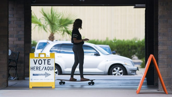 Tori Jensen, 18, rides her long board to vote at Parkway Community Church in Phoenix on Aug. 30, 2016. This was her first time voting.