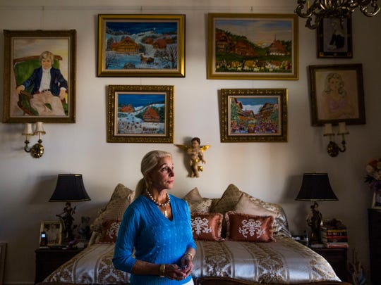 """Betsy Ross Koller, surrounded by her paintings, in her Naples home on Wednesday, March 22, 2017. Koller lost 62 of her original paintings in a fire that destroyed her studio above the garage at her home. """"You have strength you don't realize you have until you are called upon to use it,"""" Koller says."""