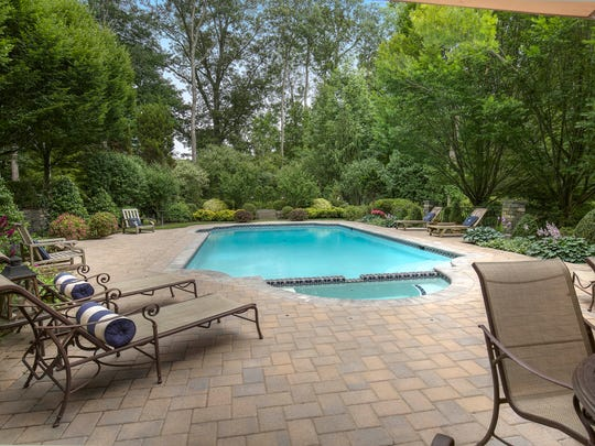 Outside the finished, walk-out basement is a paver patio surrounding an in-ground swimming pool.
