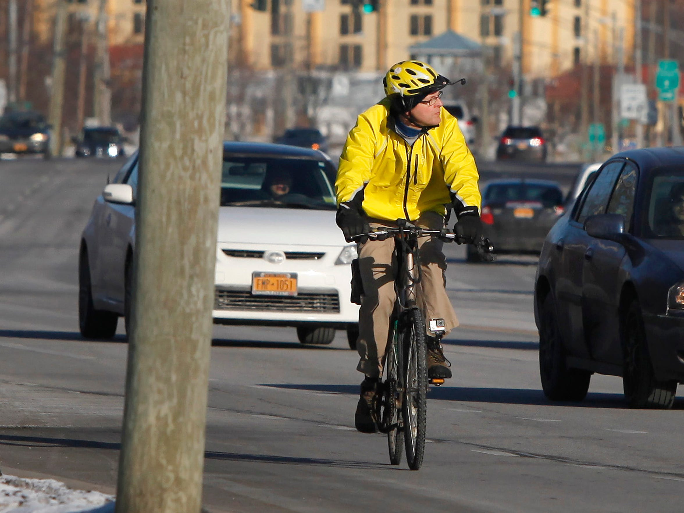 Rochester resident Scott Wagner rides his bike to work in the cold along East Henrietta Road. Wagner commutes by bike year round.