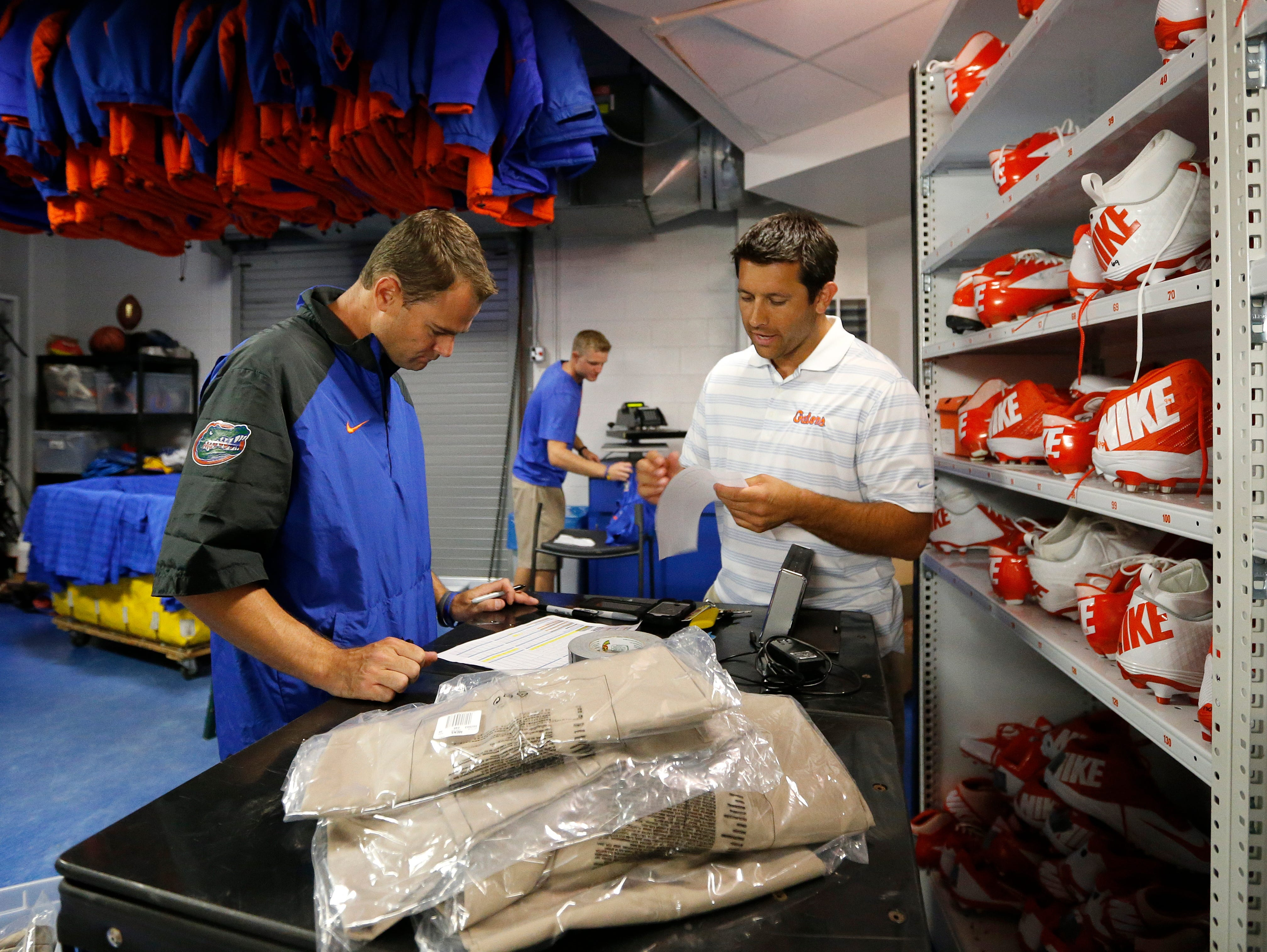 Florida assistant athletic equipment director Mike Knowles, left, and associate athletic equipment director Jeff McGrew, right, take inventory on new apparel in the Fernandez Football Equipment Room at Ben Hill Griffin Stadium in Gainesville.