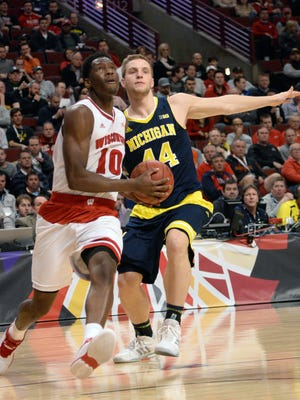 Wisconsin Badgers forward Nigel Hayes (10) is defended by Michigan Wolverines forward Max Bielfeldt during the first half of a Big Ten tournament quarterfinal at the United Center.