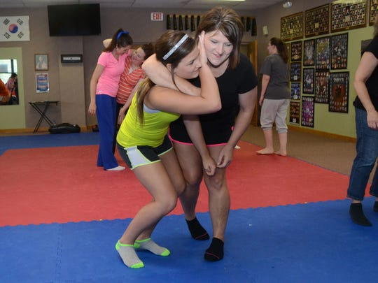 Joyce Counts (right) holds daughter Whitney Counts in a headlock as Whitney practices how to get out of it at a free self-defense class at Master Rousseau's Taekwondo held Saturday. Joyce's daughter and Whitney's sister Brittany Dowden also attended the free self defense class taught by Carol Rousseau honor of Mother's Day.
