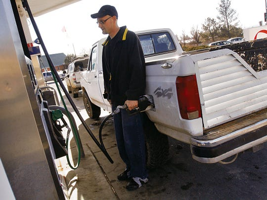 Kenneth Riaski fills up his truck Friday at the Alon location on East 30th Street and Butler Avenue in Farmington. Falling gas prices reflect the continued decline in the price of oil.