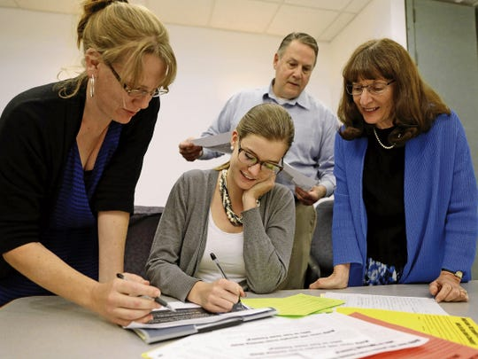 Marketing administrator Christa Romme, left, administrator Devin Shaheen, CEO Ray Hagerman and Julie Rasor, the director of administration and operations, look over materials in May at the Quality Center for Business building at San Juan College in Farmington.