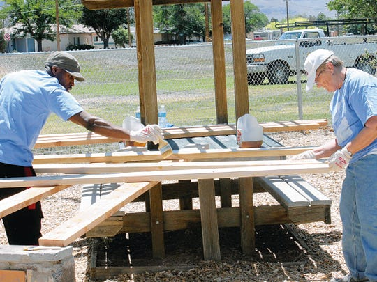 In this file photo from May 2014, Taj Cypress of Holloman Air Force Bases's 49th LRS, left, and Karen Pagel, a community volunteer, waterproofed lumber at Kids Kingdom in an effort to repair, beautify and preserve the park through the annual Great American Cleanup event.