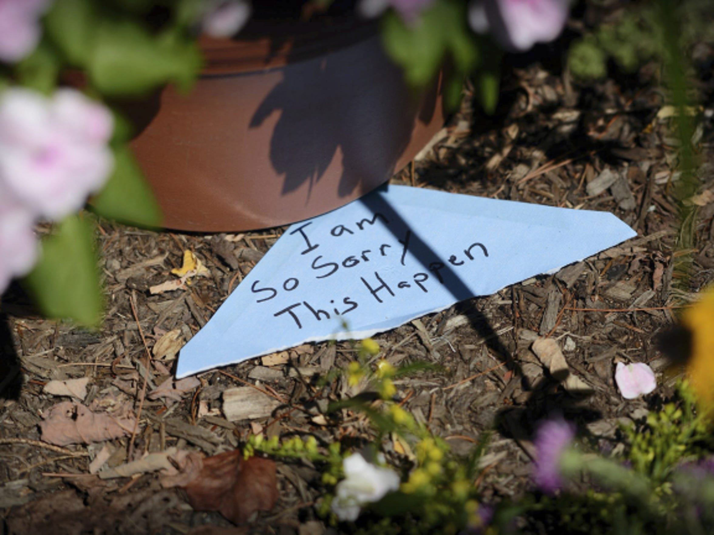 The note expressing sympathy for the shooting death of Stacey Pennington rests on the ground in the Fairy Garden outside the Gretna Emporium gift shop, which Pennington owned.